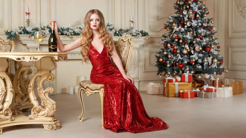 圣诞节装饰风格背景下穿着红色礼服裙的金发美女