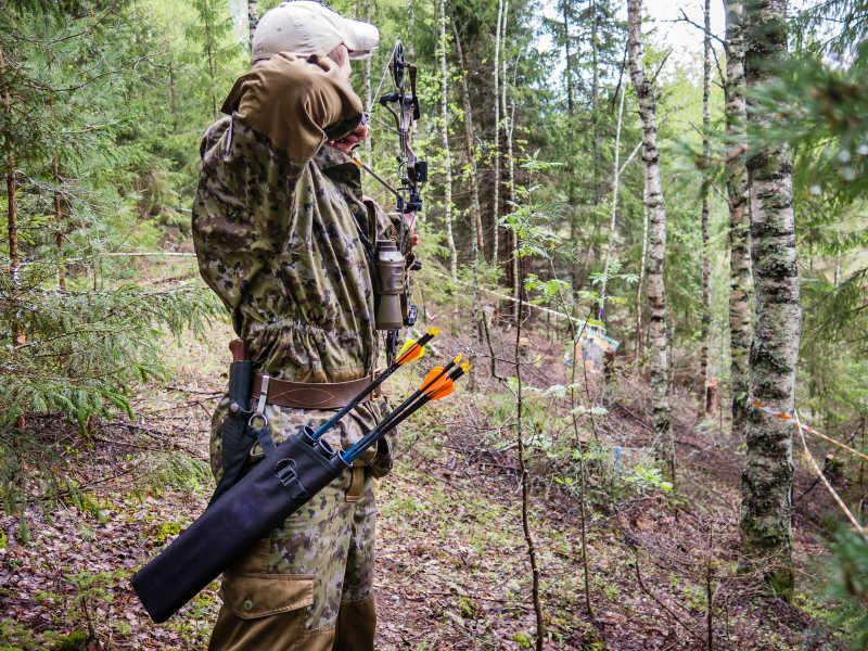 瞄准室外目标的男子弓箭手