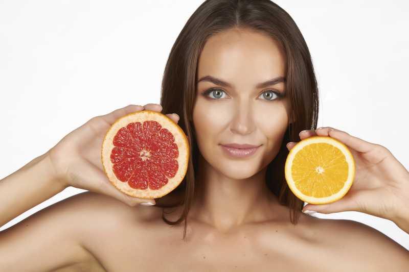 美丽性感的美女拿着橙子