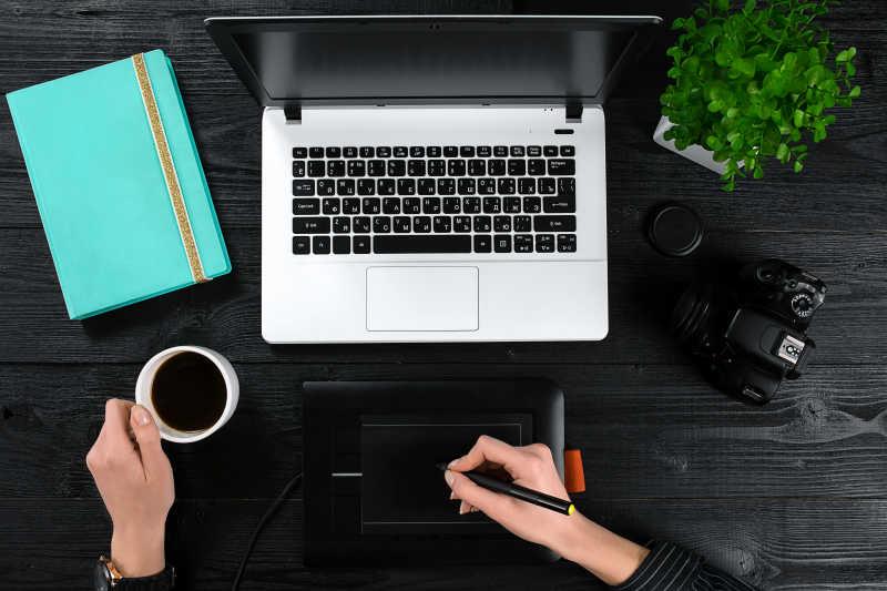 女性手拿着一杯咖啡,在黑色木桌上的笔记本电脑前的笔记本上写字