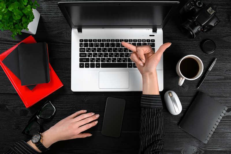 一位穿着黑色衬衫的女士在桌上对着笔记本电脑比着手势