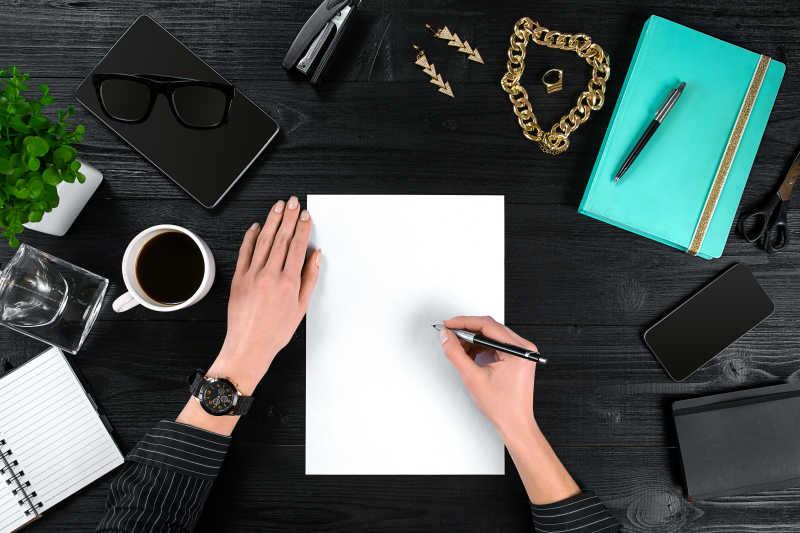 在黑色办公桌上写字办公的女性