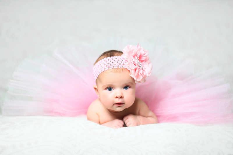 可爱的小女孩在穿着漂亮的粉红色喇叭裙