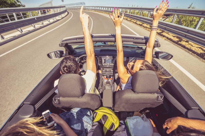 一组人在敞篷车上开心的周游世界