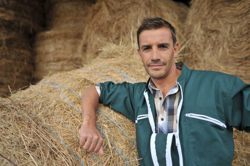 站在干草卷前的快乐农民