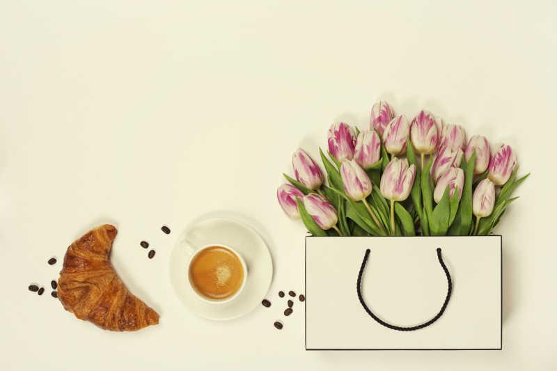 咖啡牛角包和购物袋里的郁金香