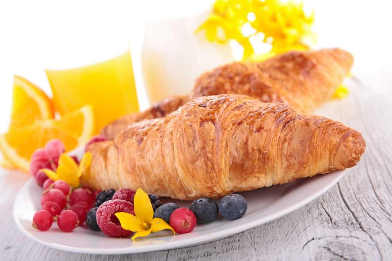 白色盘子上的牛角面包和水果