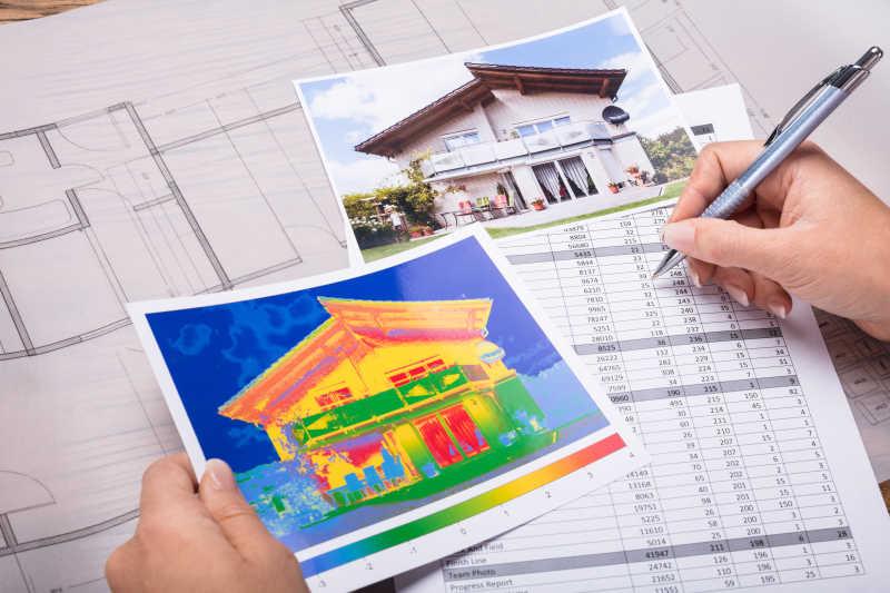 一名建筑设计师手拿笔正在奋笔疾书