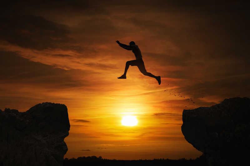 日落时分,一个人在夕阳下跳过深渊的剪影