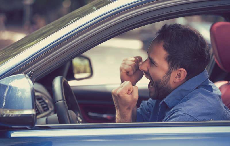 坐在车内的司机愤怒的举起拳头尖叫