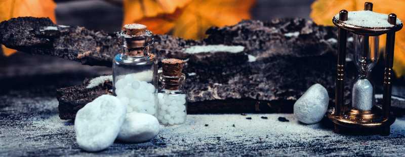 自然疗法中的沙漏白色药丸和鹅卵石