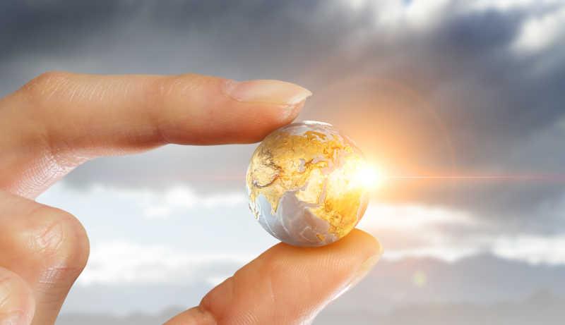 太阳阳光下的手拿概念地球
