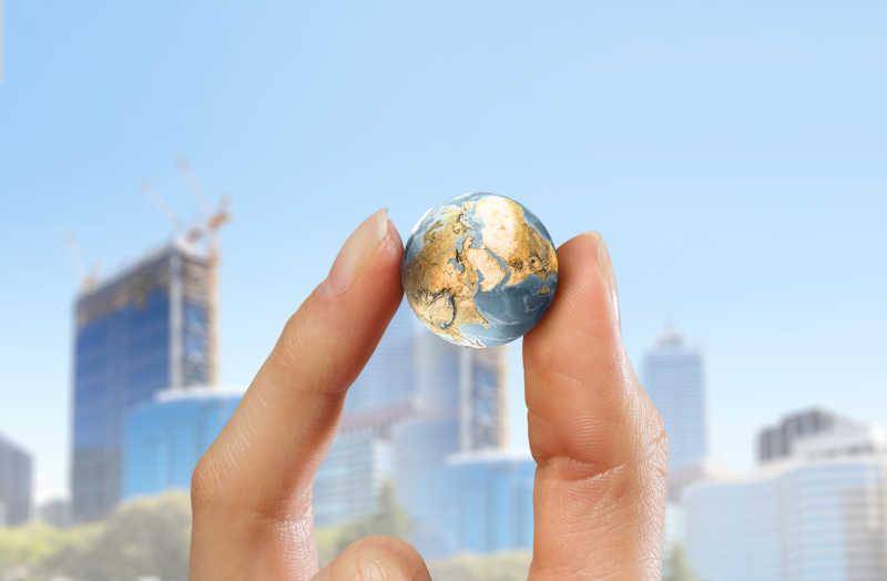 虚化的城市背景下的手拿概念地球