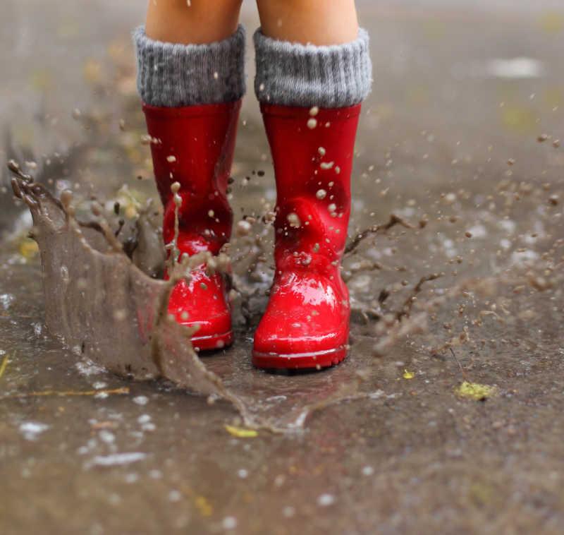 穿红靴子跳进水坑的孩子