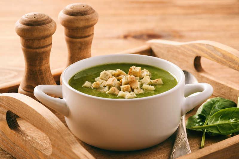 与木质托盘奶油汤旁边还有调羹菠菜叶