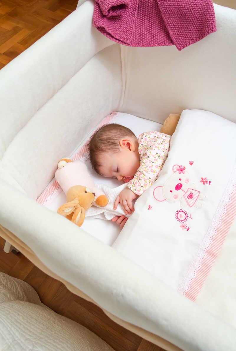 可爱的小女孩睡在婴儿床含着奶嘴抱着毛绒玩具