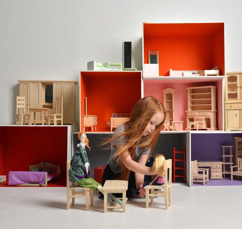 坐在地上玩着小型桌椅和娃娃的可爱小女孩