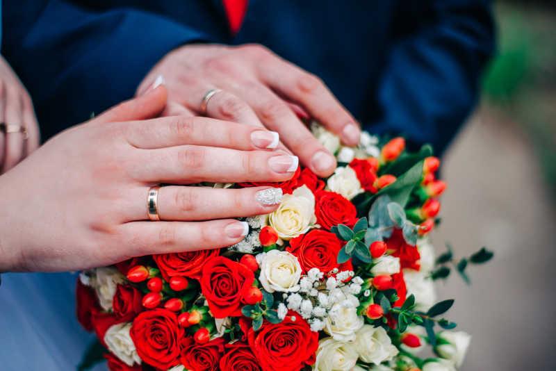 新婚夫妇戴着戒指的手放在捧花上