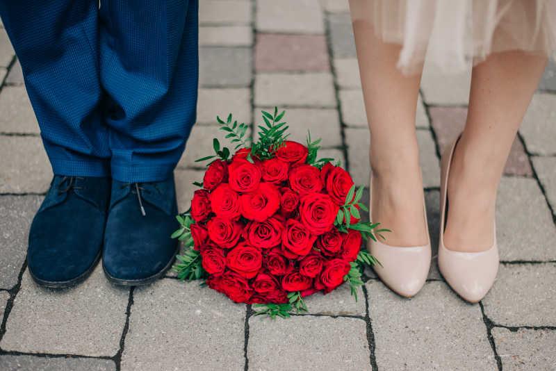 新婚夫妇脚之间的红玫瑰捧花