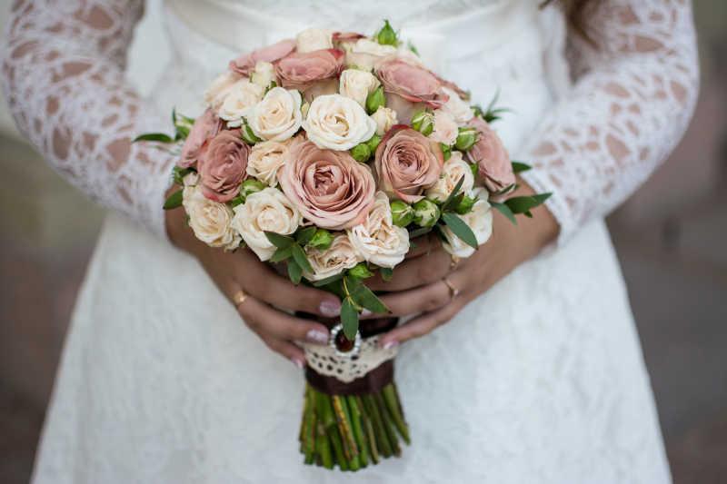 新娘手拿玫瑰捧花特写