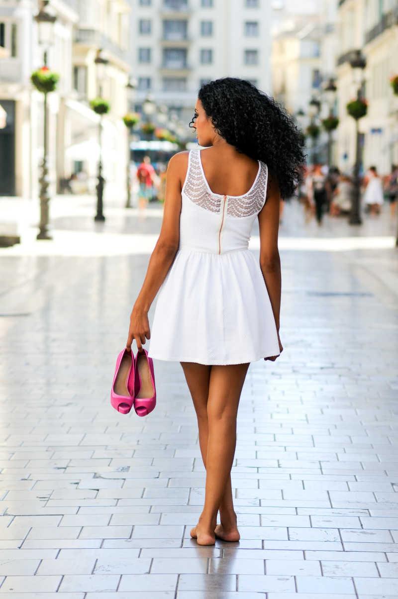 拿着高跟鞋站在街角的年轻女模特