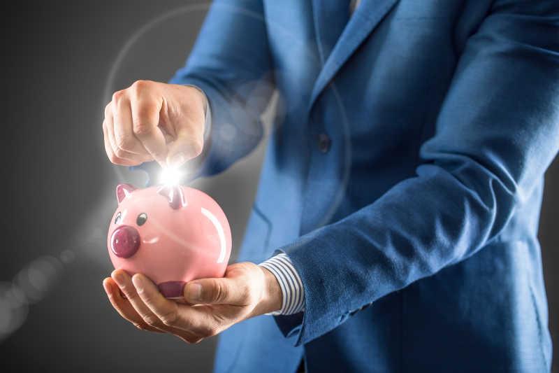 拿着桃红色小猪和放硬币的商人