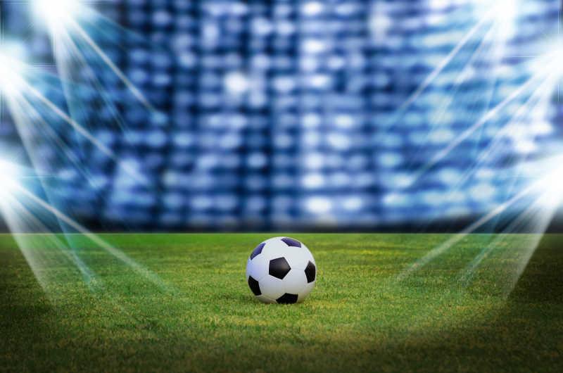 聚光灯下的草地上的足球