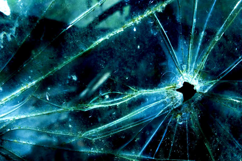 在碎玻璃的子弹孔特写