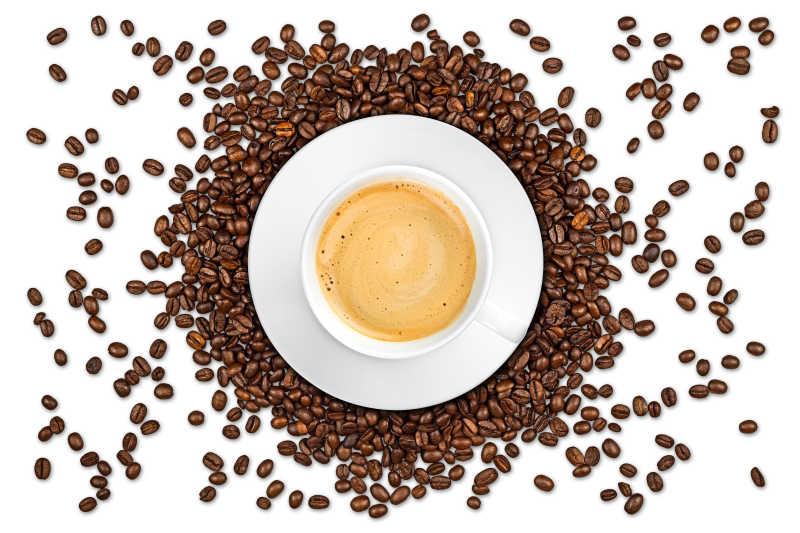 围绕着咖啡杯的咖啡豆