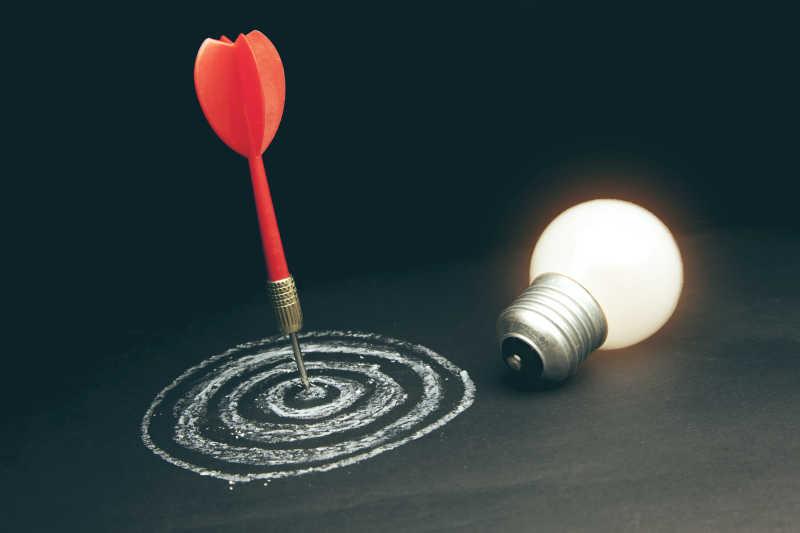 飞镖集中靶心和亮着的灯泡