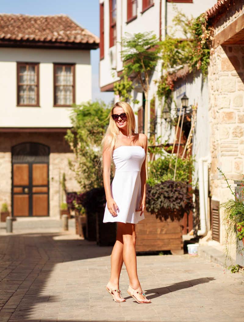 穿着白色裙子的美女走在古老旅游小镇上