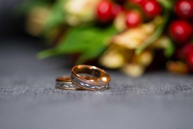 虚化捧花背景下的结婚对戒特写