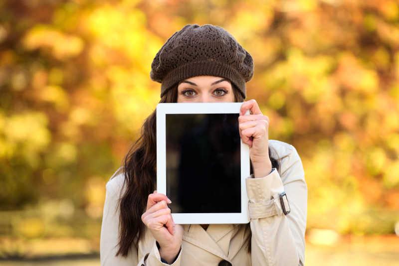 手拿平板电脑站在秋天落叶下的女人