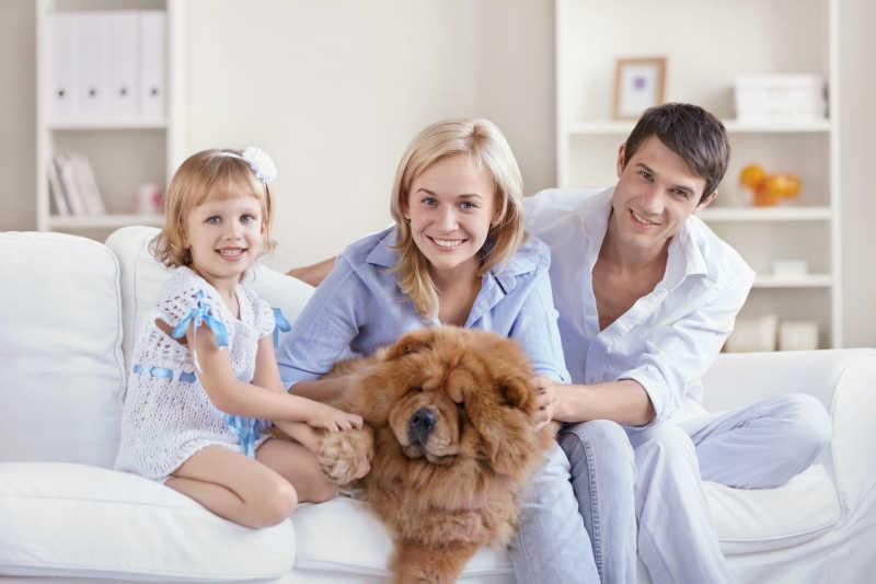 沙发上的三口之家和宠物狗