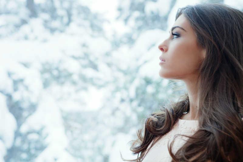 冬季室内透过窗户看着室外雪景的年轻人