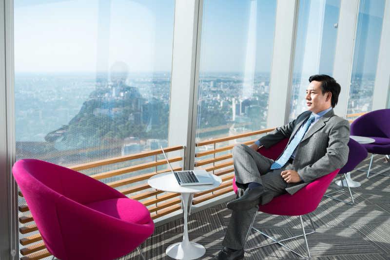 通过办公室窗口看城市的沉思商人