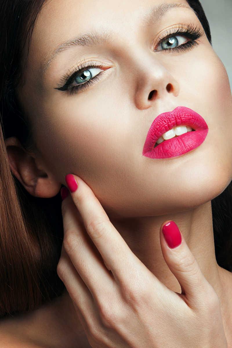 粉色口红和美甲的西方化妆模特