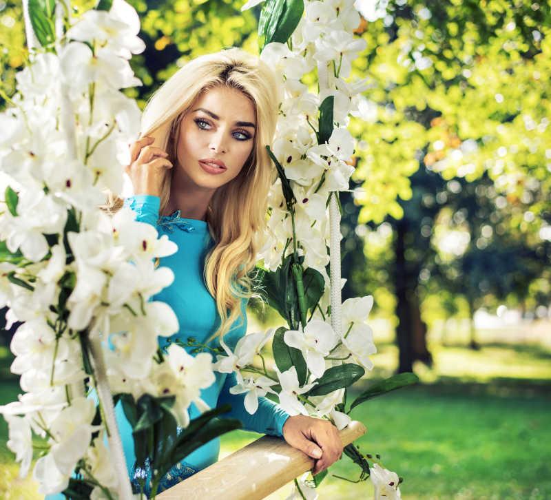 漂亮的金发美女站在美丽的秋千旁