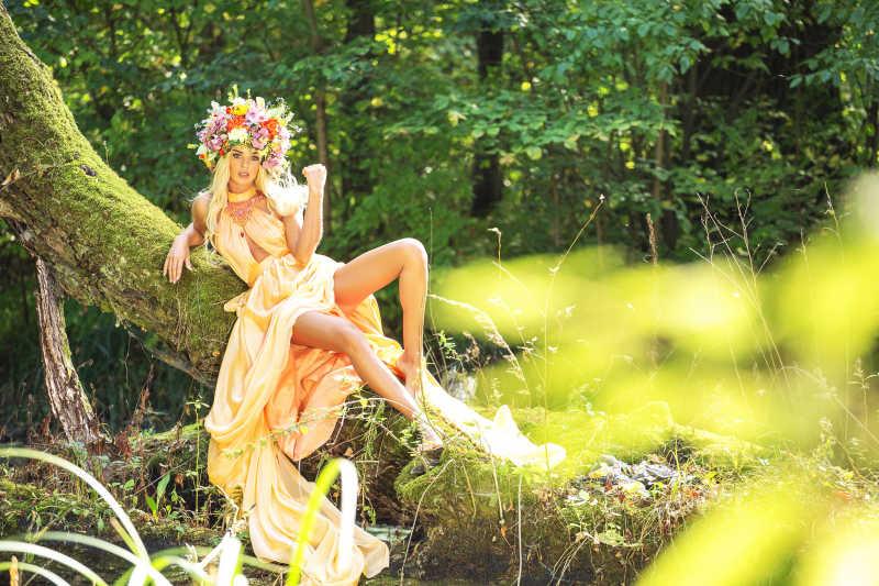躺在树干上头戴花环的金发美女