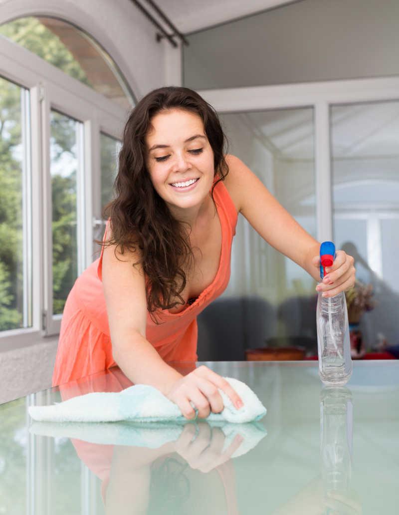 女青年在客厅用清洁剂和抹布擦玻璃桌