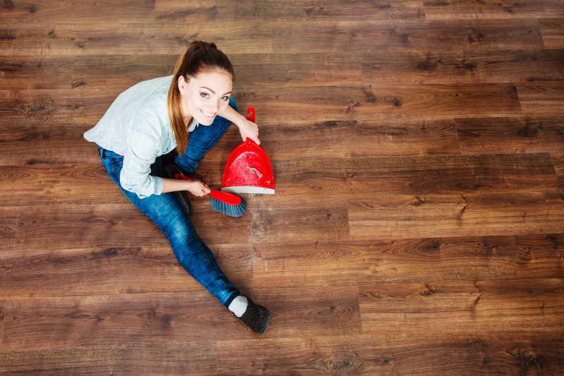 家务清理用红色小笤帚和簸箕扫木地板