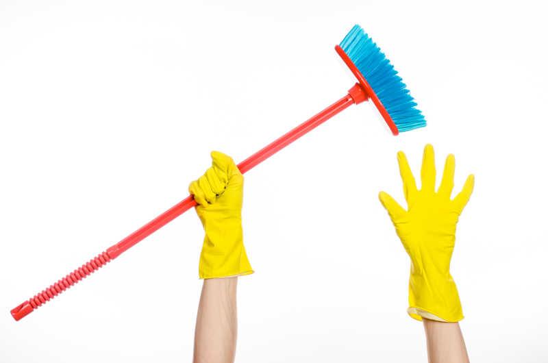戴着黄色橡胶手套手持一把红色扫帚特写