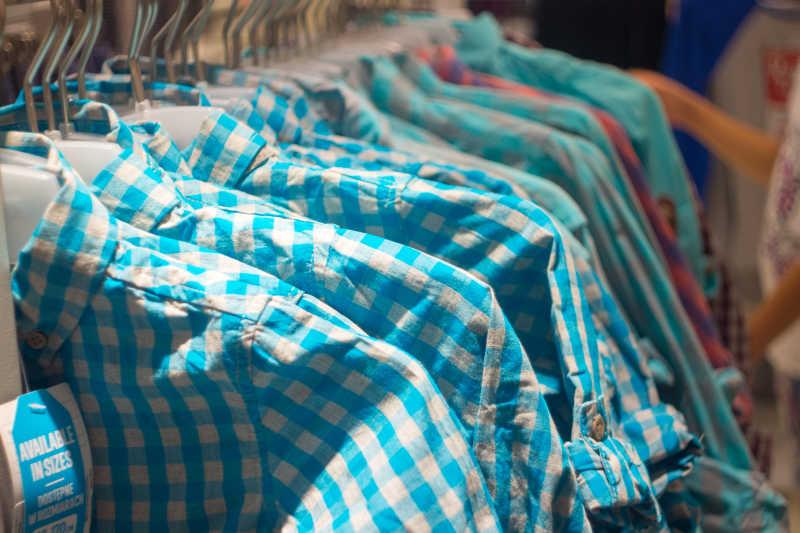 陈列在衣架上的各种时髦的衬衫