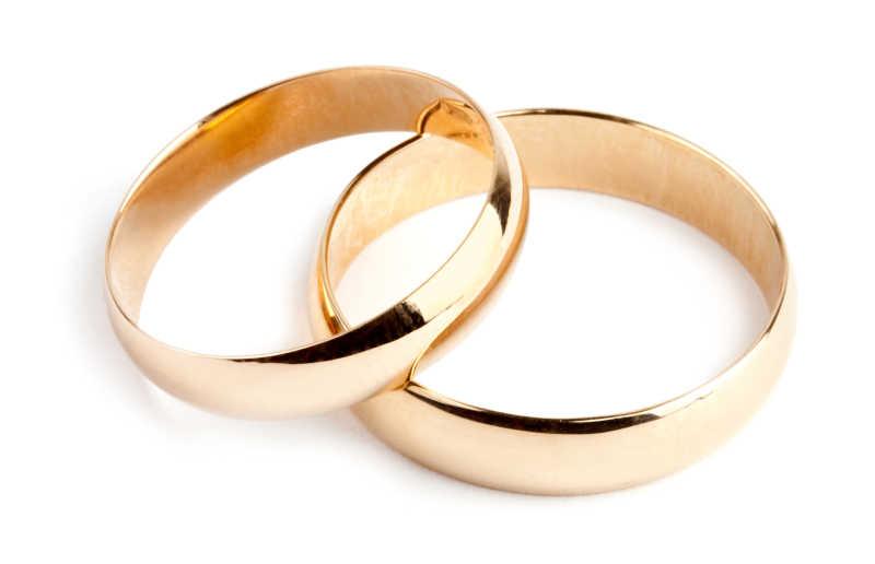 白色背景上的两枚金戒指