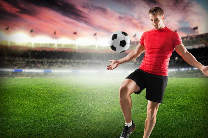 红色云朵下体育场的足球运动员