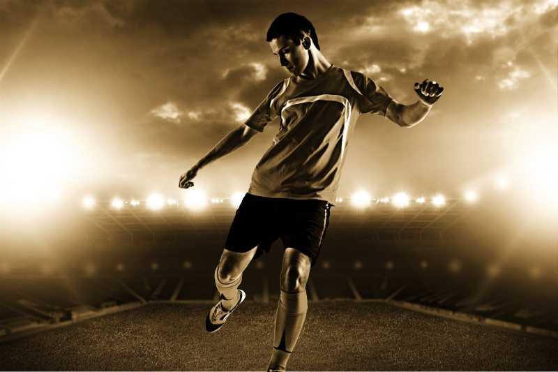 聚光背景下运动场的足球运动员