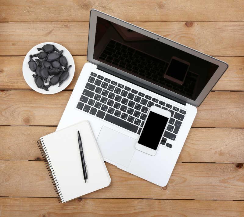 打开笔记本日记和带糖果碟的智能手机