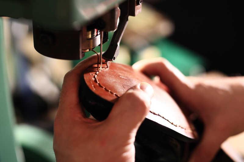 鞋匠利用机器缝鞋底特写