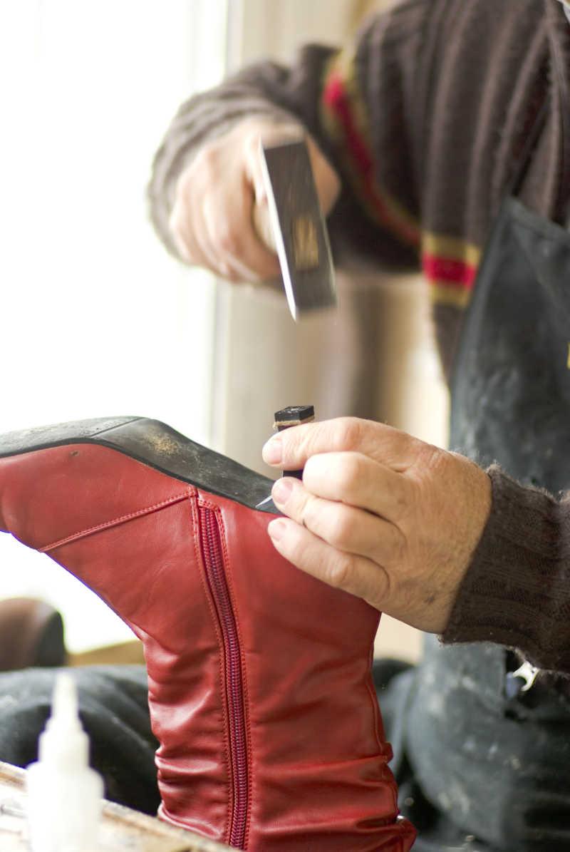 鞋匠修理红色高跟鞋特写