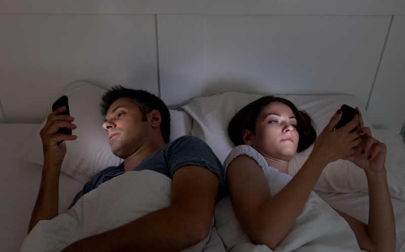 睡觉前看着手机的夫妇